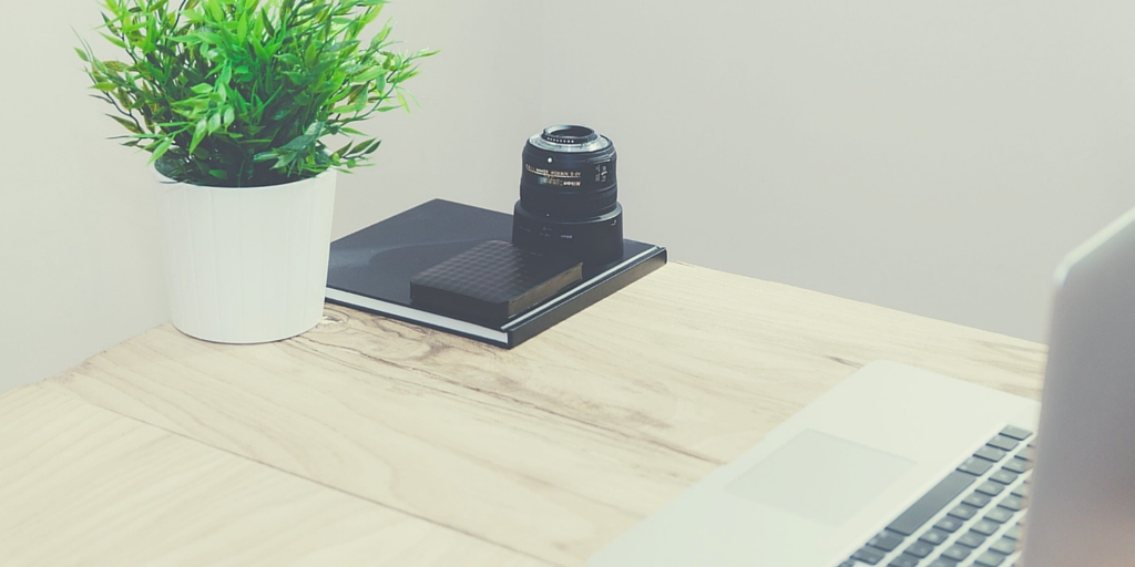 Wooden desk with green pot plant, camera lense, and a MacBook
